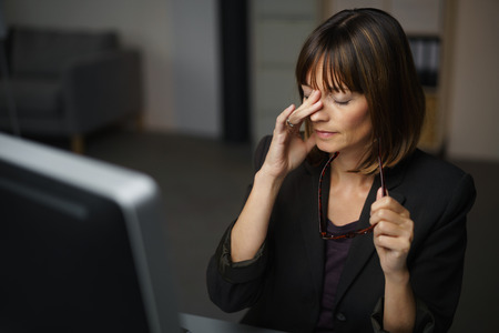 headache pain: Tired Businesswoman Sitting at her Table, Takes Off her Eyeglasses and Rubs her Eyes Stock Photo