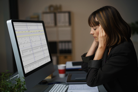 employment: Side View of a Tired Businesswoman Working on her Computer at her Table, Holding her Head with Eyes Closed. Stock Photo