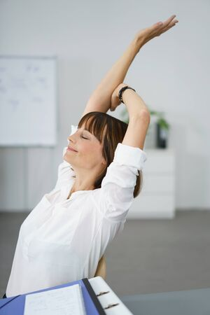 working stiff: Thoughtful Businesswoman Sitting at her Table and Stretching her Arms with Eyes Closed and Happy Facial Expression. Stock Photo