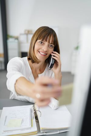 independent contractor: Happy Businesswoman Talking to Someone on her Phone While Putting a Sticky Note for Reminders on the Side of her Computer Monitor.