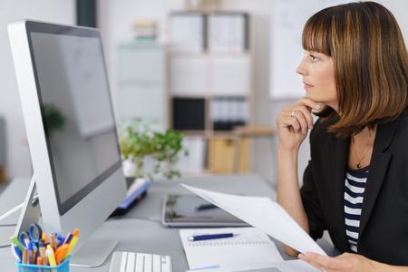 profil: Widok z boku z businesswoman patrząc na jej Ekran komputera Poważnie trzymając Dokumenty.