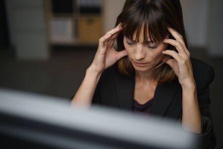 throbbing: Businesswoman suffering from a headache or migraine holding her hands to her throbbing temples as she works late in the office to a deadline