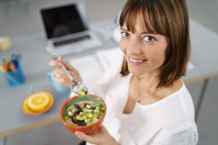 pert: Office Woman Sitting at her Desk, Smiles at the Camera While Holding her Healthy Meal in a Bowl.