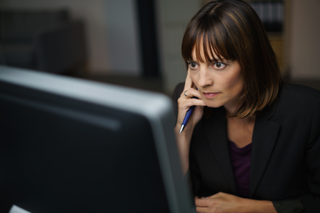 perturbed: Intense young businesswoman working late at the office sitting at her desk in the darkness staring at her desktop monitor