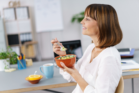 woman eat: Side View of a Happy Businesswoman Having a Meal at her Desk Inside the Office
