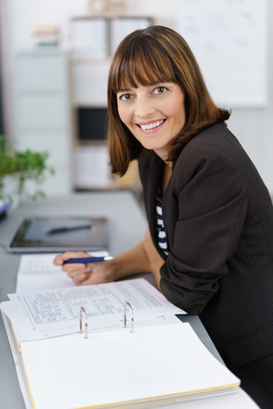 lovely businesswoman: Successful businesswoman with a lovely warm friendly smile sitting working at her desk in the office turning to look at the camera