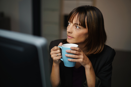distance: Thoughtful Businesswoman Sitting at her Table, Holding a Cup of Coffee and Looking Into the Distance Seriously.