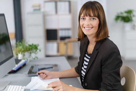 authority: Half Body Shot of a Happy Businesswoman Working on Business Documents at her Table, Smiling at the Camera. Stock Photo