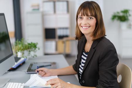 autoridad: La mitad de tiro del cuerpo de un De negocios feliz que trabaja en los documentos de negocios en su mesa, sonriendo a la cámara.
