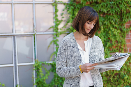 immersed: Businesswoman standing outside the window of a building with a green creeper on the wall reading documents in files she is holding with a serious expression