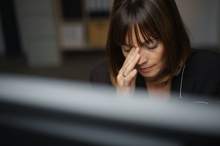 throbbing: Businesswoman under pressure working late in the office in the darkness suffering from a stress headache and holding her hand to the bridge of her nose as she sits behind a desktop monitor Stock Photo