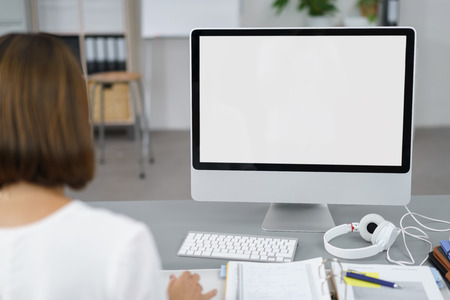 Businesswoman Working on her Computer with Copy Space on Monitor at her Desk Inside the Office. Stock Photo