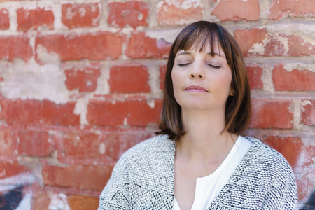 Close up Thoughtful Woman Leaning Against Old Brick Wall with Eyes Closed.