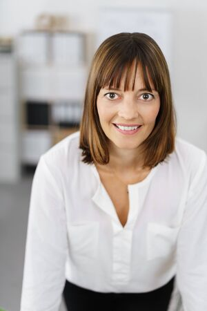 mesmerising: Portrait of a Businesswoman Leaning on her Table Inside the Office Smiling at the Camera. Stock Photo