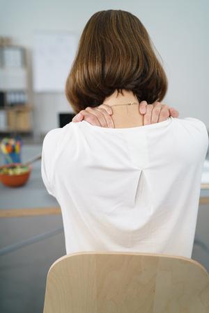 sillon: Vista trasera de una oficina de la mujer cansada que se sienta en su escritorio, masaje de la parte posterior del cuello con las dos manos.