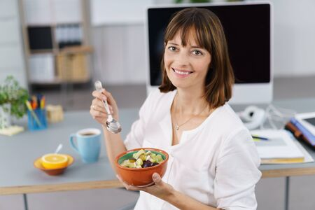 Smiling businesswoman enjoying a healthy fruit salad as she sits at her desk in the office during her lunch break Stock Photo
