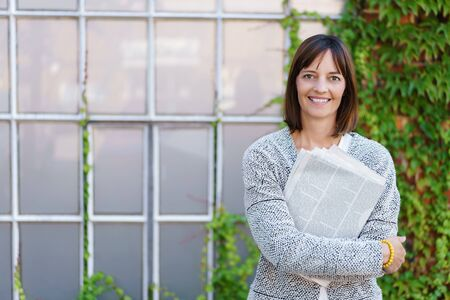 windowpanes: Half Body Shot of a Happy Businesswoman Hugging Newspaper and Smiling at the Camera Against Building Background Stock Photo