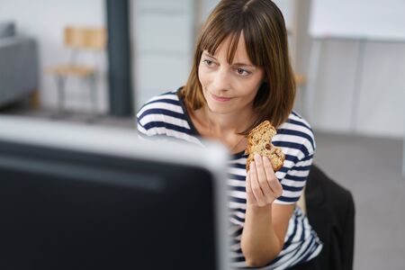 woman eating cake: Office Woman Holding a Bread Snack While Working on her Computer at her Table. Stock Photo
