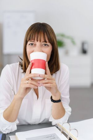 Happy Businesswoman Drinking a Cup of Coffee at her Desk While Looking at the Camera. Stock Photo
