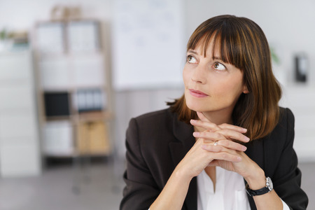 inscrutable: Close up Pensive Businesswoman Sitting at her Table, Looking Up with Fingers Crossed.