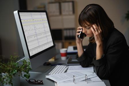Moe zakenvrouw in gesprek met een cliënt van mobiele telefoon tijdens het werken op de computer en een aantal zakelijke documenten. Stockfoto