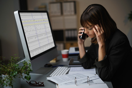 concerned: Tired Businesswoman Talking to a Client by Mobile Phone While Working on Computer and Some Business Documents. Stock Photo