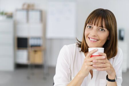 energising: Close up Happy Office Woman Holding a Cup of Coffee with both Hands and Smiling at the Camera.