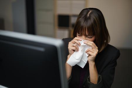 Geschäftsfrau mit einem saisonalen Winter Fieber und Kälte ihre Nase weht auf einem weißen Taschentuch, wie sie sitzt im Schatten in ihrem Büro