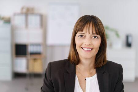 mujer sola: Cerrar una feliz Empresaria Dentro de la oficina, mirando a la cámara con una sonrisa con dientes