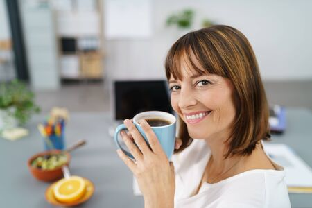 work addicted: Happy Office Woman Sitting at her Desk, Holding a Cup of Coffee and Smiling at the Camera.