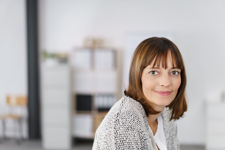 office workers: Head and Shoulder Shot of an Adult Office Woman Looking at the Camera with Half Smile Face.