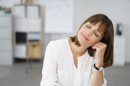 woman at work: Portrait of a Thoughtful Office Woman with Eyes Closed, Leaning her Face on her hand with Happy Facial Expression.