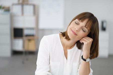 gente pensando: Retrato de una mujer pensativa con la Oficina Ojos cerrados, apoyando la cara en la mano con la expresión facial feliz. Foto de archivo