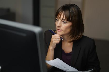 Donna di affari seria che lavora al suo computer a sua scrivania all'interno dell'ufficio. Archivio Fotografico