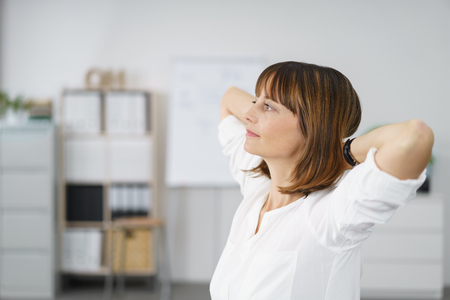 Pensive Office Woman with Hands Behind her Head and Looking to the Left of the Frame.