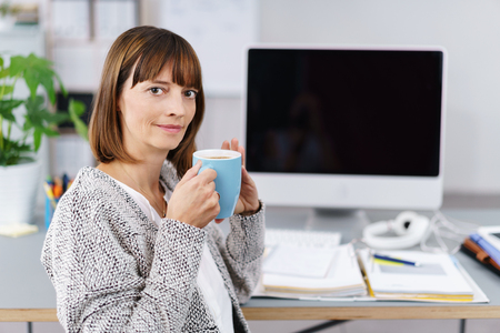 hot secretary: Office woman holding a cup of coffee with blank pc screen in background