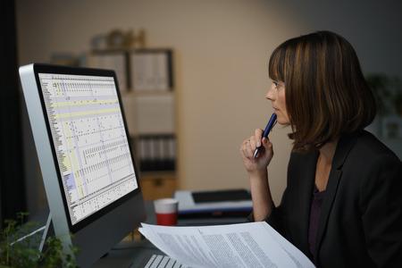 gente trabajando: La mitad Shot Cuerpo de una empresaria inteligente trabajando en su computadora en serio con la pluma en la barbilla. Foto de archivo