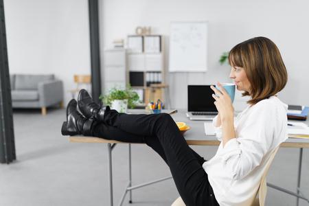 relajado: Pensativo mujer de oficina con una taza de café y mirando a la distancia con las piernas sobre la mesa.