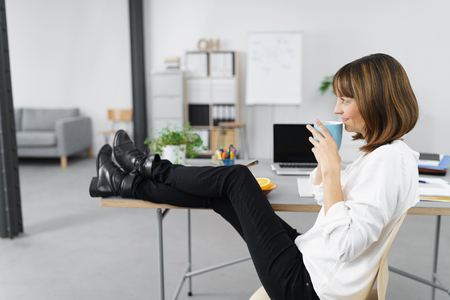 Thoughtful Office Woman Holding a Cup of Coffee and Looking Into the Distance with Legs on the Table.