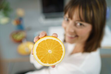 workplace wellness: Happy Office Woman at her Desk Showing a Fresh Sliced Orange at the Camera in Close up.