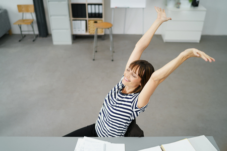 high angle shot: High Angle Shot of a Thoughtful Office Woman Sitting at her Desk, Stretching her Arms Up with Happy Facial Expression Stock Photo