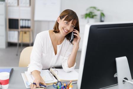 secretarias: Feliz empresaria sentado en su escritorio, hablando con alguien por teléfono móvil mientras se trabaja en su ordenador