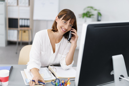 Happy Businesswoman Sitting at her Desk, Talking to Someone on Mobile Phone While Working on her Computer