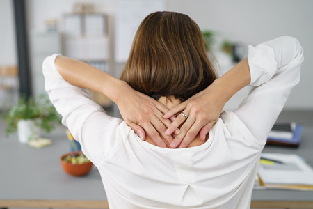 cansancio: Cierre de vista trasera de una empresaria cansada que sostiene la nuca con las dos manos.