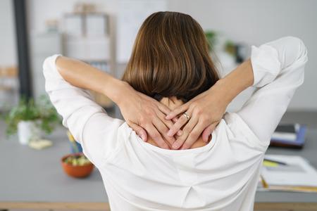 Close-up Rear View van een vermoeide zakenvrouw bedrijf haar nek met twee handen. Stockfoto