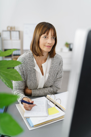 content writing: Businesswoman Working on her Computer with Notes at her Desk In the Office.