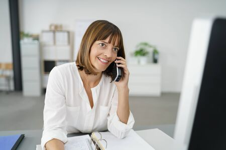 fulfilled: Happy Businesswoman at her Table, Talking to Someone Using her Mobile Phone Stock Photo
