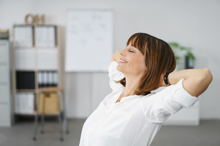 éxtasis: Feliz Pensativa Empresaria con las manos sosteniendo detrás de su cabeza, se relaja en su oficina.