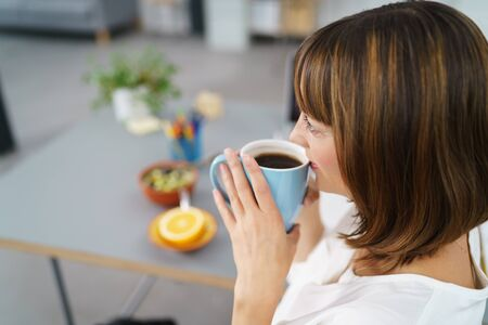 energising: Close up Thoughtful Office Woman Drinking Coffee in a Cup While Sitting at her Desk and Looking Into the Distance. Stock Photo
