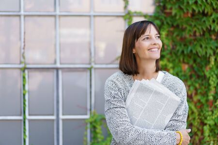 half body: Half Body Shot of a Happy Woman Holding Newspaper and Looking Up Outside the Office